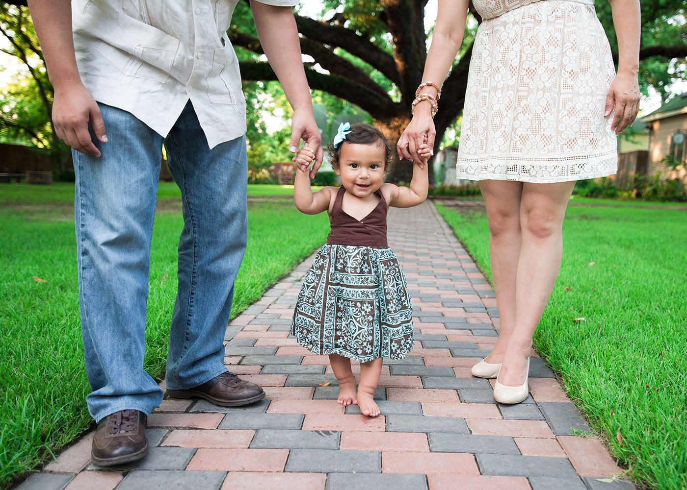 Held by her parents hand, Katalina walks her path.