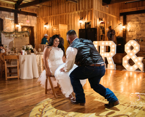 Bride has fun while groom takes her garter off